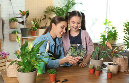 Mother and daughter taking care of plants at home