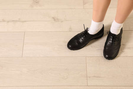 Child in school shoes indoors, closeup of legs. Space for text