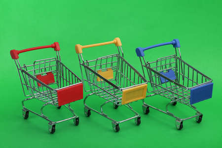 Row of empty shopping trolleys on color background Stockfoto