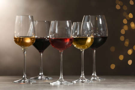 Glasses with different wines on grey table against defocused lights 写真素材