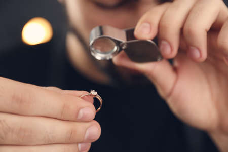 Male jeweler evaluating ring in workshop, closeup Stockfoto