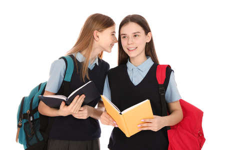 Portrait of teenage girls in school uniform with backpacks and books on white background