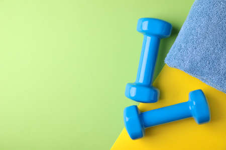Vinyl dumbbells and towel on color background, flat lay. Space for text