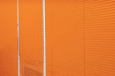 Window with closed orange blinds as background