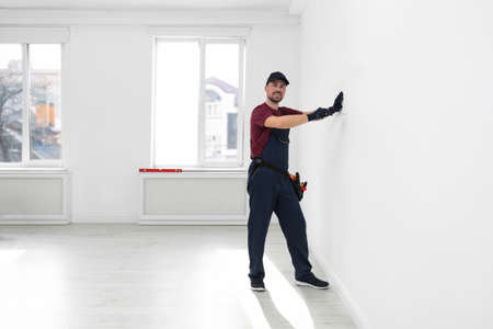 Handyman in uniform working with screwdriver indoors, space for text. Professional construction tools