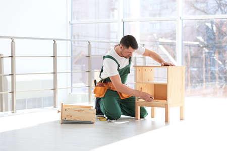 Handyman in uniform assembling furniture indoors. Professional construction tools