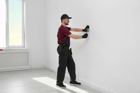 Handyman in uniform working with hammer indoors. Professional construction tools Imagens