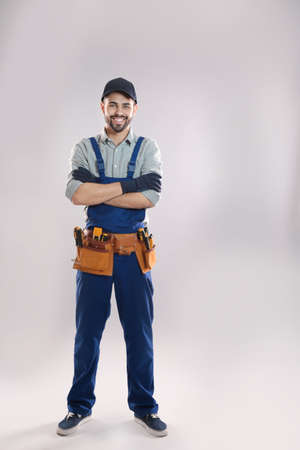 Full length portrait of construction worker with tool belt on light background
