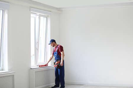 Handyman in uniform working with building level indoors, space for text. Professional construction tools Stock Photo