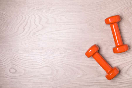 Vinyl dumbbells and space for text on wooden background, flat lay