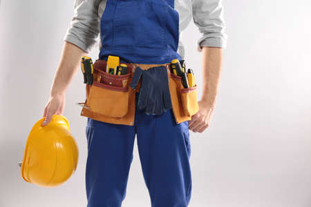 Construction worker with hard hat and tool belt on light background, closeup. Space for text Stock Photo