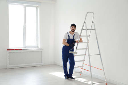 Full length portrait of handyman with roller brush near ladder indoors, space for text. Professional construction tools