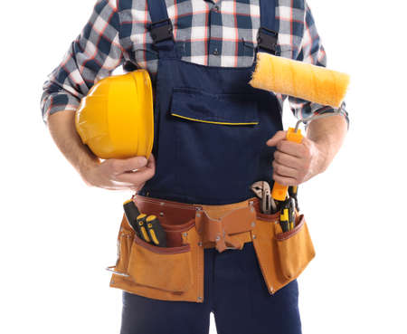Construction worker with hard hat, paint roller and tool belt on white background, closeup Stock Photo
