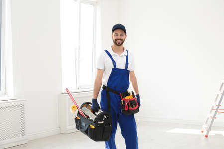 Portrait of professional construction worker with tools indoors