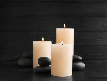 Burning candles and spa stones on table. Space for text
