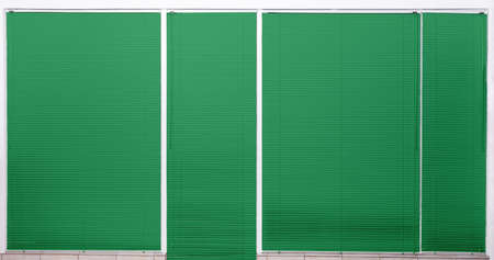 Modern window with closed stylish green blinds