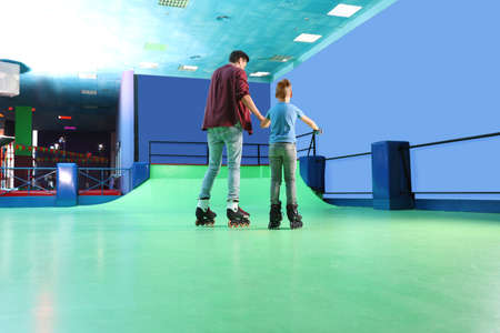 Father teaching his son roller skating at rink Banco de Imagens