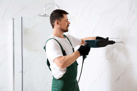 Handyman working with drill in bathroom. Professional construction tools