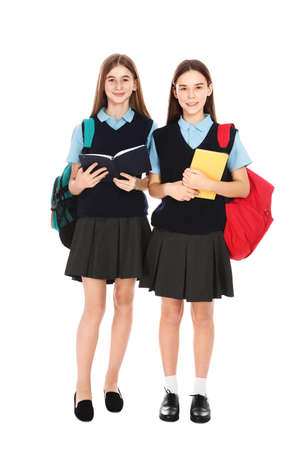 Full length portrait of teenage girls in school uniform with backpacks and books on white background