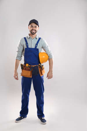 Full length portrait of construction worker with hard hat and tool belt on light background Stock Photo