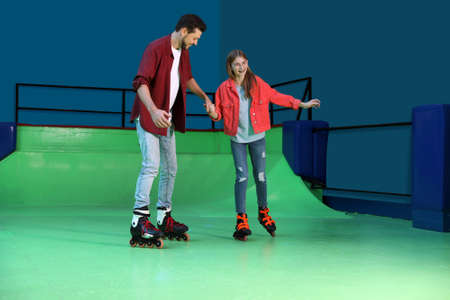 Father teaching her daughter roller skating at rink