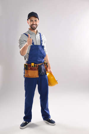 Full length portrait of construction worker with hard hat and tool belt on light background Banco de Imagens