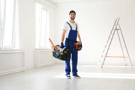 Full length portrait of professional construction worker with tools indoors