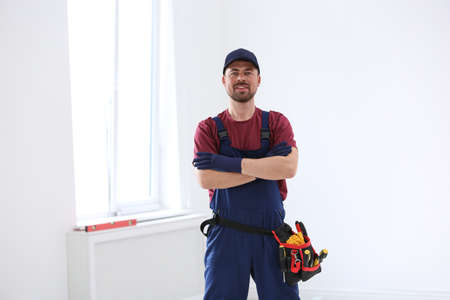 Portrait of professional construction worker with tool belt indoors Stock Photo