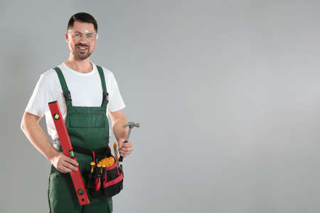 Portrait of professional construction worker with tools on grey background, space for text