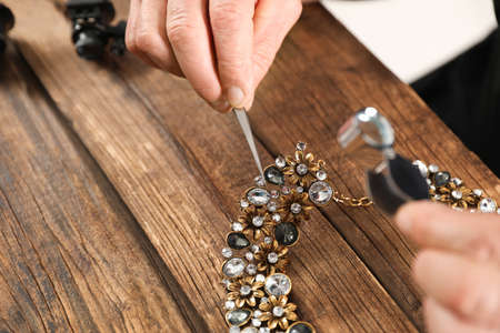 Male jeweler evaluating necklace at table in workshop, closeup. Space for text Stock Photo