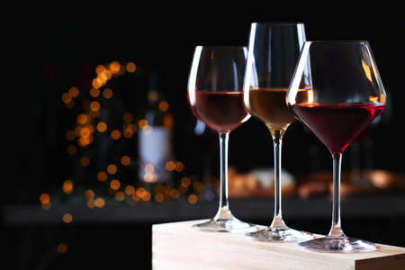 Glasses with different wines on wooden table against defocused lights. Space for text