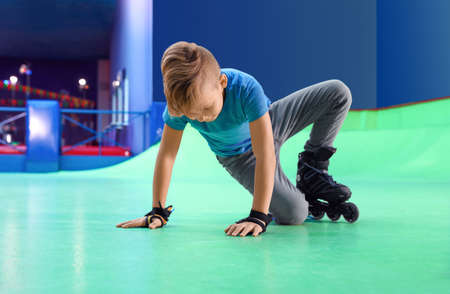 Boy falling down at roller skating rink