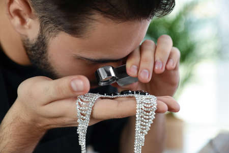 Male jeweler evaluating beautiful necklace in workshop, closeup