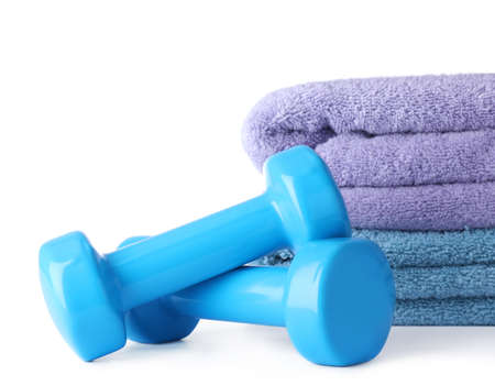 Stylish dumbbells and towels on white background. Home fitness Imagens - 124878356