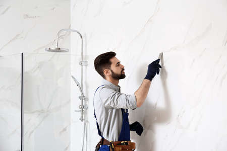 Handyman working in bathroom. Professional construction tools