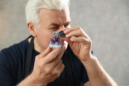 Male jeweler evaluating semi precious gemstone in workshop