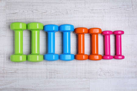 Many colorful dumbbells on table, flat lay. Fitness equipment Imagens