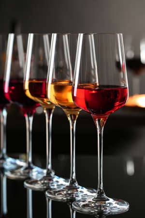 Row of glasses with different wines on bar counter against blurred background
