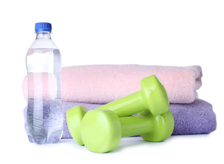 Stylish dumbbells, bottle of water and towels on white background. Home fitness Imagens