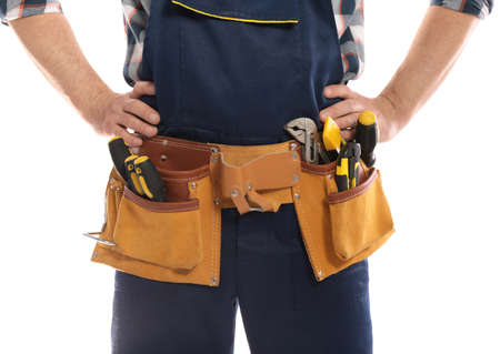 Professional construction worker with tool belt on white background, closeup Stock Photo