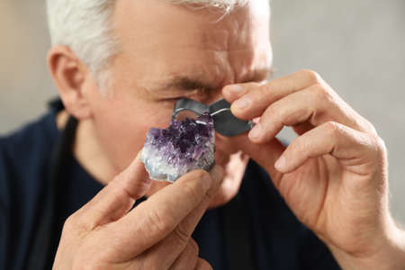 Male jeweler evaluating semi precious gemstone in workshop, closeup Imagens