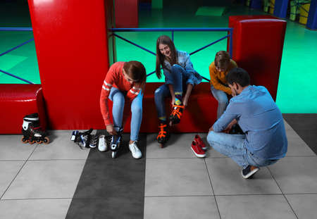 Happy family putting on roller skates indoors Stock Photo