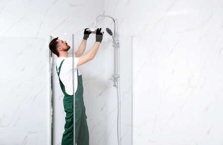 Professional handyman working in shower booth indoors, space for text