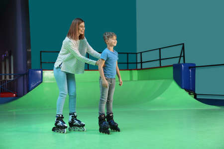 Woman teaching her son roller skating at rink. Space for text