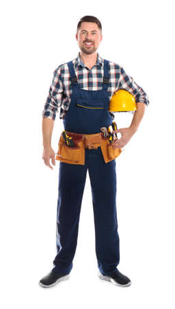 Full length portrait of professional construction worker with hard hat and tool belt on white background