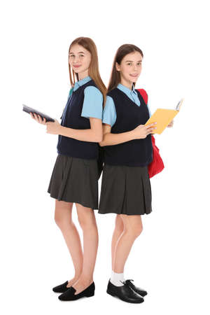 Full length portrait of teenage girls in school uniform with books on white background Banco de Imagens