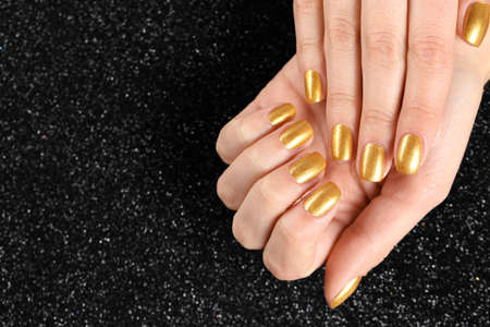 Woman showing manicured hands with golden nail polish on black background, closeup. Space for text Фото со стока