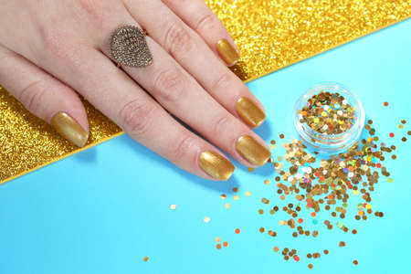 Woman showing manicured hand with golden nail polish and glitter on color background, closeup