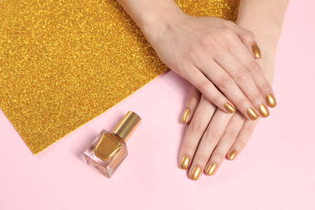 Woman showing manicured hands with golden nail polish on color background, closeup