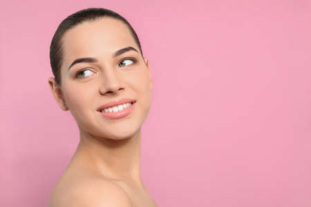 Portrait of young woman with beautiful face and natural makeup on color background, space for text